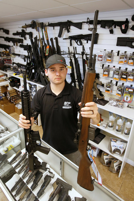 """Salesman Ryan Martinez holds an AR-15, (L) and a Springfield M1-A, (R) both semi-automatics guns at the """"Ready Gunner"""" gun store in Provo, Utah, U.S., June 21, 2016. (Photo by George Frey/Reuters)"""