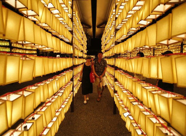 People walk among paper lanterns during the annual Mitama Festival at the Yasukuni Shrine in Tokyo July 13, 2014. Over 30,000 lanterns light up the precincts of the shrine, where more than 2.4 million war dead are enshrined, during the four-day festival. The festival goes on till July 16. (Photo by Yuya Shino/Reuters)