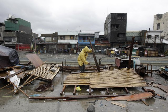 A man salvages what is left of his makeshift house as Typhoon Rammasun batters suburban Navotas, north of Manila, Philippines on Wednesday, July 16, 2014. (Photo by Aaron Favila/AP Photo)