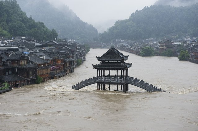 This picture taken on July 15, 2014 shows a bridge submerged in floodwaters in the ancient town of Fenghuang, central China's Hunan province. Rainstorms lashed central China's Hunan Province and southwest China's Guizhou Province, affecting over 1 million people and flooding a historical town, state media reported. (Photo by AFP Photo)