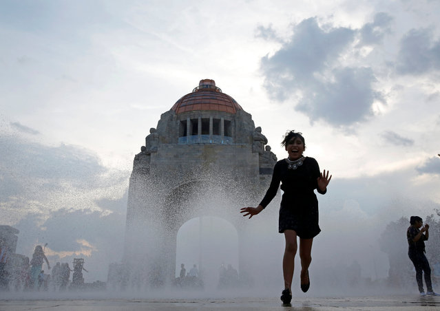 A  woman runs through a fountain at the Monument of the Revolution in Mexico City, Mexico August 5, 2017. (Photo by Henry Romero/Reuters)