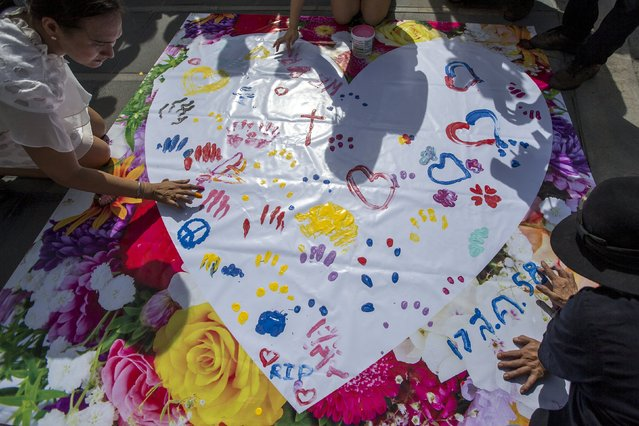 People leave messages on a banner for victims killed in Monday's bomb blast during a religious ceremony near at the Erawan shrine, the site of Monday's deadly blast, in central Bangkok, Thailand, August 21, 2015. (Photo by Athit Perawongmetha/Reuters)