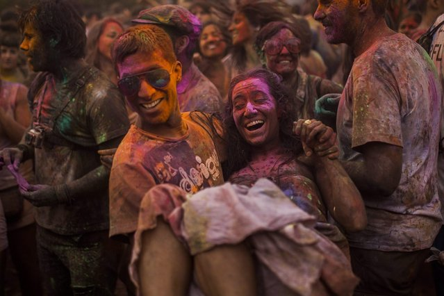 A man carries a woman as revelers throw special coloured powders over each other, during a Monsoon Holi Festival in Madrid, Spain, Saturday, August 9, 2014.The festival is based on the Hindu spring festival Holi, also known as the festival of colours where participants colour each other with dry powder and coloured water. (Photo by Andres Kudacki/AP Photo)