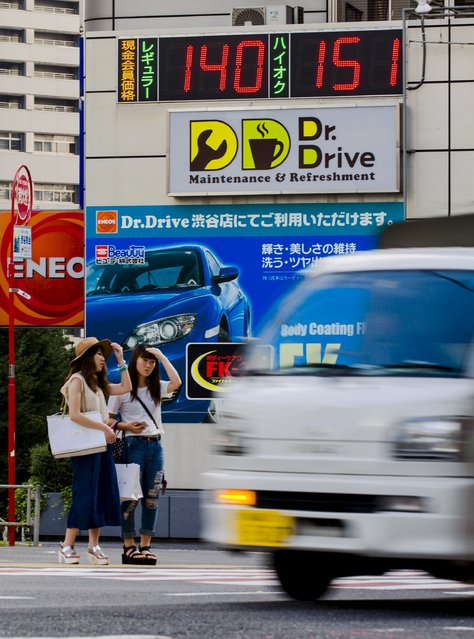 A vehicle drives past a LED sign at a petrol station displaying its current fuel prices in yen in Tokyo August 24, 2015. Oil prices hit 6-1/2-year lows on Monday after Chinese stock markets suffered their biggest one-day fall since the global financial crisis, intensifying worries over the outlook for global oil demand. (Photo by Thomas Peter/Reuters)