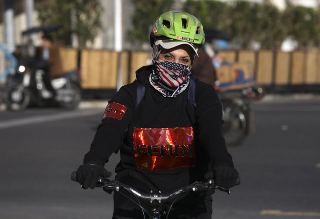 A woman rides her bicycle covering her face with a scarf depicting the U.S. flag, in downtown Tehran, Iran, Monday, March 2, 2020. A member of a council that advises Iran's supreme leader died Monday after falling sick from the new coronavirus, becoming the first top official to succumb to the illness striking both citizens and leaders of the Islamic Republic. (Photo by Vahid Salemi/AP Photo)
