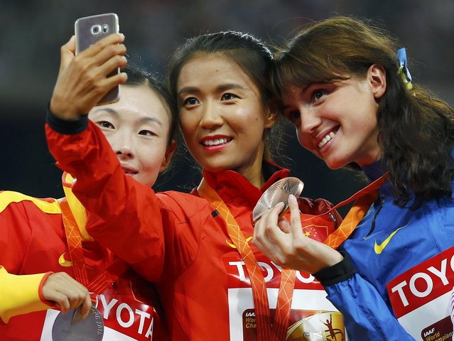 Liu Hong of China, gold medal, (C) takes a selfie with Lu Xiuzhi of China (L), silver medal, and Lyudmyla Olyanovska of Ukraine (R), bronze medal, as they pose on the podium after the women's 20 km race walk event during the 15th IAAF World Championships at the National Stadium in Beijing, China, August 28, 2015. (Photo by Damir Sagolj/Reuters)