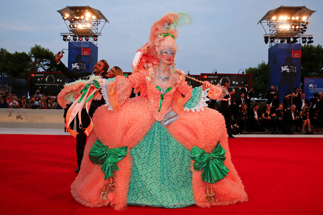 """A guest poses at the red carpet for the movie """"Ammore e malavita"""" during the 74th Film Festival in Venice, Italy on September 6, 2017. (Photo by Alessandro Bianchi/Reuters)"""