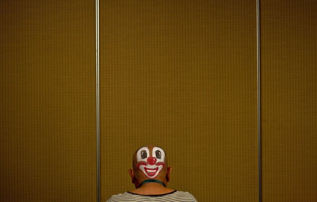 A clown prepares to take part in a Clown Festival in Kuala Lumpur on August 17, 2014. (Photo by Manan Vatsyayana/AFP Photo)