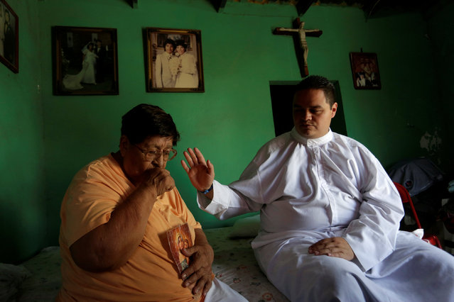 An aspiring Catholic priest Jose Luis Guerra, a member of Raza Nueva in Christ, a project of the archdiocese of Monterrey, blesses a woman with diabetes at her home in Monterrey, Mexico, July 13, 2016. (Photo by Daniel Becerril/Reuters)