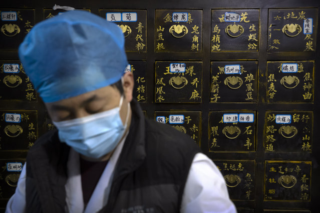 In this March 13, 2020 photo, a worker fills orders for prescriptions in front of a cabinet of drawers containing ingredients for traditional Chinese medicine preparations at the Bo Ai Tang traditional Chinese medicine clinic in Beijing. With no approved drugs for the new coronavirus, some people are turning to alternative medicines, often with governments promoting them. (Photo by Mark Schiefelbein/AP Photo)