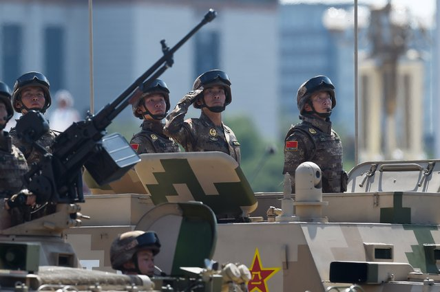 Soldiers ride in Chinese military vehicles as they are paraded through Tiananmen Square in Beijing on September 3, 2015 during a military parade to mark the 70th anniversary of victory over Japan and the end of World War II. (Photo by Wang Zhao/Reuters)