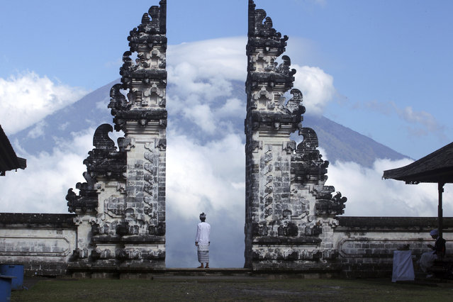 Balinese man watches Mount Agung volcano almost covered with clouds as he stands at a temple in Karangasem, Bali, Indonesia, Tuesday, September 26, 2017. An increasing frequency of tremors from the volcano indicates magma is continuing to move toward the surface and an eruption is possible, a disaster agency official said Tuesday. Tourists are cutting short their stay to the island, where an eruption would force the airport to close and strand thousands. (Photo by Firdia Lisnawati/AP Photo)