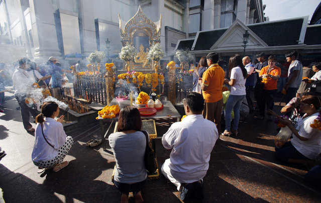 Visitors pray at Phra Phrom, the Thai interpretation of the Hindu god Brahma, at the Erawan Shrine in Bangkok, Thailand, Friday, September 4, 2015. Thai authorities unveiled the restored centerpiece Friday of the Erawan Shrine, in the latest bid to restore confidence among Bangkok's tourism and business communities almost three weeks after a deadly bombing. (Photo by Sakchai Lalit/AP Photo)