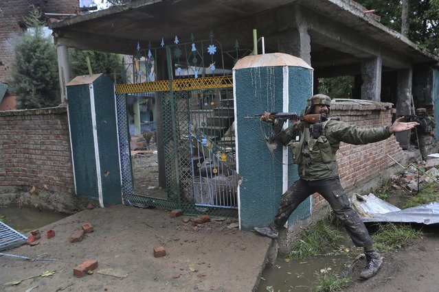 An Indian army solider shouts to his colleague to throw a magazine loaded with bullets during a gunbattle in Rajpora village south of Srinagar, India, Tuesday, September 2, 2014. Indian government forces killed three suspected rebels in a gunbattle Tuesday in the disputed Himalayan region of Kashmir, where many residents oppose India's decades-long rule, officials said. (Photo by Dar Yasin/AP Photo)