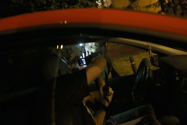 "A zombie approaches a car during the ""Survival Zombie"" competition in Collado Villalba, outside Madrid, late September 6, 2014. According to the back-story of the ""Survival Zombie"" contest, participants, who signed up as survivors, are trapped for a night in a city that has been infected with a virus that causes humans to turn into zombies. (Photo by Susana Vera/Reuters)"
