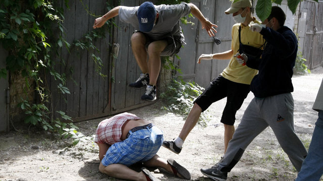 Unidentified people beat Svyatoslav Sheremet (L, bottom), head of Gay-Forum of Ukraine public organization, in Kiev, May 20, 2012. Sheremet was attacked after meeting with members of the media to inform them that a scheduled gay parade was cancelled. The attackers ran off when they realised members of the media were documenting the attack. (Photo by Anatolii Stepanov/Reuters)
