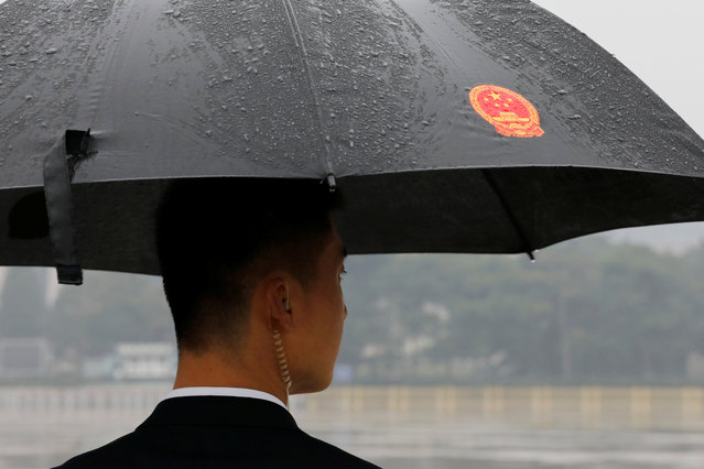 A plainclothes solider stands guard in the rain outside the Great Hall of the People before the opening of the 19th National Congress of the Communist Party of China in Beijing, China on October 18, 2017. (Photo by Tyrone Siu/Reuters)