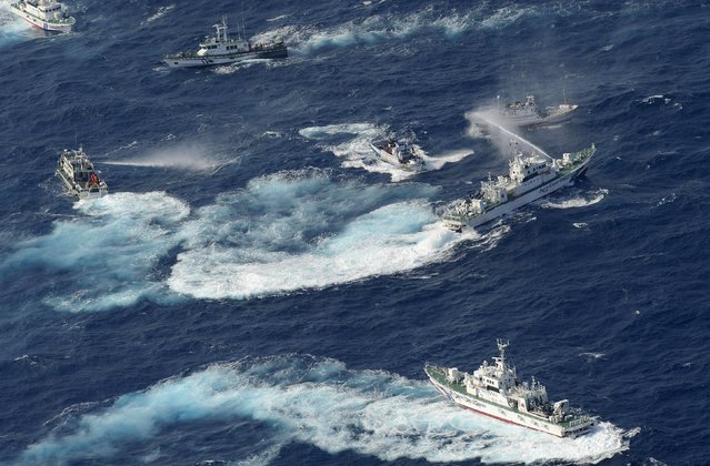 A Japan Coast Guard vessel (R) sprays water against Taiwanese fishing boats, while a Taiwanese coast guard ship (L) also sprays water in the East China Sea near Senkaku islands as known in Japanese or Diaoyu Islands in Chinese on September 25, 2012.  Coastguard vessels from Japan and Taiwan duelled with water cannon after dozens of Taiwanese boats escorted by patrol ships sailed into waters around the Tokyo-controlled islands. (Photo by Yomiuri Shimbun/AFP)