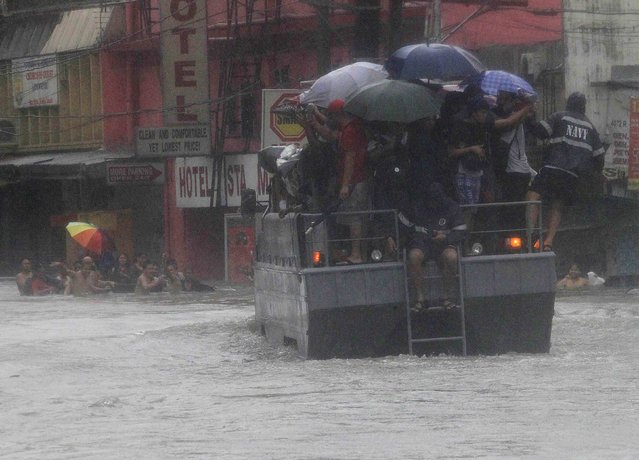 Stranded passengers ride on a navy truck to cross a flooded street after tropical storm Fung-Wong battered metro Manila September 19, 2014. (Photo by Romeo Ranoco/Reuters)