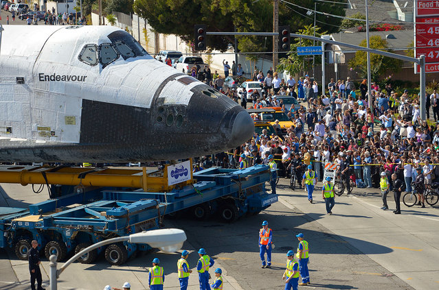 The Space Shuttle Endeavour is moved slowly along a city street October 12, 2012, in Los Angeles, California. The shuttle is on its last mission – a 12-mile creep through city streets, past an eclectic mix of strip malls, mom-and-pop shops, tidy lawns and faded apartment buildings. Its final destination is the California Science Center in South Los Angeles where it will be put on display.  (Photo by Mark J. Terrill-Pool)
