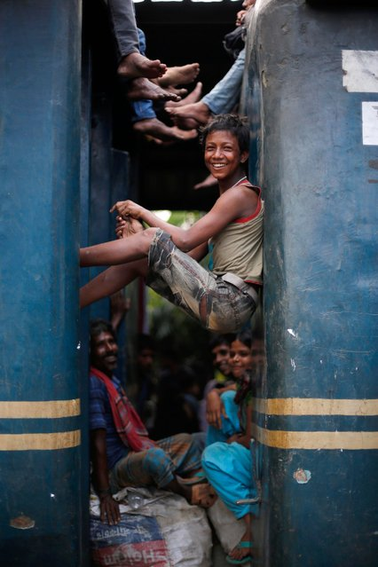 People sit between two compartments of an overcrowded train in an attempt to travel to their villages ahead of the Eid Al-Adha celebrations, at the Airport Railway Station in Dhaka, Bangladesh, October 3, 2014. Millions of people travel back to their villages to celebrate the major festival. (Photo by Abir Abdullah/EPA)