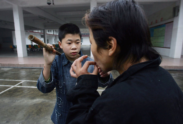 Chinese kids share a cigarette at an assistance center February 23, 2005 in Shenzhen, Guangdong Province, China. (Photo by Cancan Chu/Getty Images)