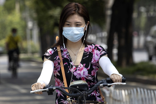 A woman wearing a mask to curb the spread of the new coronavirus rides an electric bike on the streets of Beijing on Friday, June 19, 2020. China declared a fresh outbreak in Beijing under control after numbers for new cases stabilized as hundreds of thousands are tested. (Photo by Ng Han Guan/AP Photo)