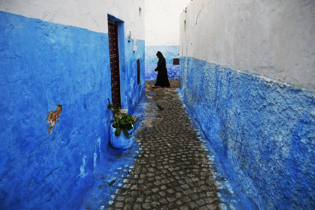 A woman makes her way between houses painted in traditional blue and white colours in Kasbah of the Udayas, a picturesque ancient part of Rabat September 21, 2014. (Photo by Damir Sagolj/Reuters)