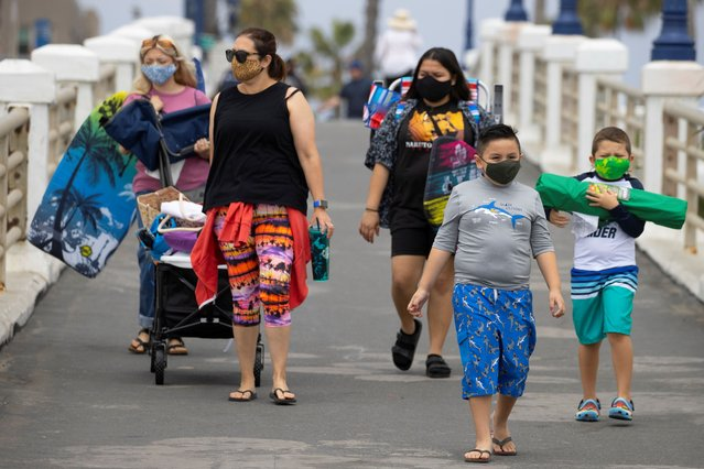 People wear face masks as they arrive at the beach during the global outbreak of the coronavirus disease (COVID-19) in Oceanside, California, U.S., June 22, 2020. (Photo by Mike Blake/Reuters)