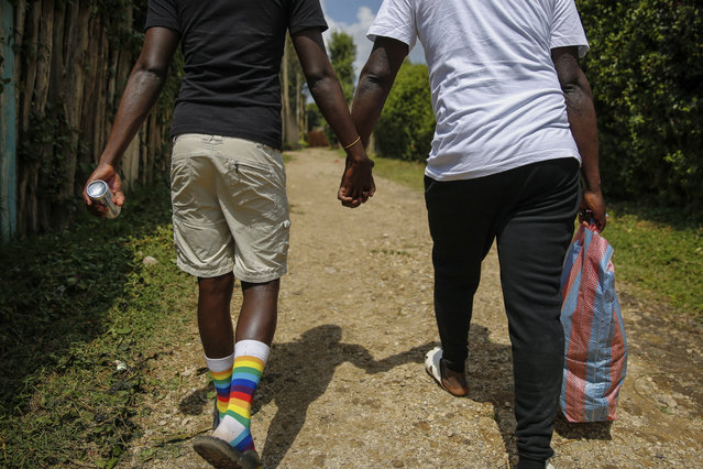 In this photo taken Thursday, June 11, 2020, gay Ugandan refugees Chris Wasswa, left, and Kasaali Brian, right, return after shopping for food in Nairobi, Kenya. Members of the LGBT community in East Africa face discrimination that has forced many to flee to Kenya, which has become a haven for them. (Photo by Brian Inganga/AP Photo)