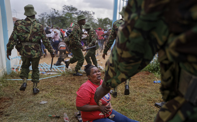 A woman who fell begs for mercy during clashes between rock-throwing supporters of President Uhuru Kenyatta and police at his inauguration ceremony after they tried to storm through gates to get in and were tear-gassed, at Kasarani stadium in Nairobi, Kenya Tuesday, November 28, 2017. (Photo by Ben Curtis/AP Photo)