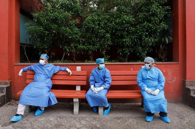 Health workers wearing Personal Protective Equipment (PPE) sit on a bench at a crematorium in New Delhi, India, June 24, 2020. (Photo by Anushree Fadnavis/Reuters)