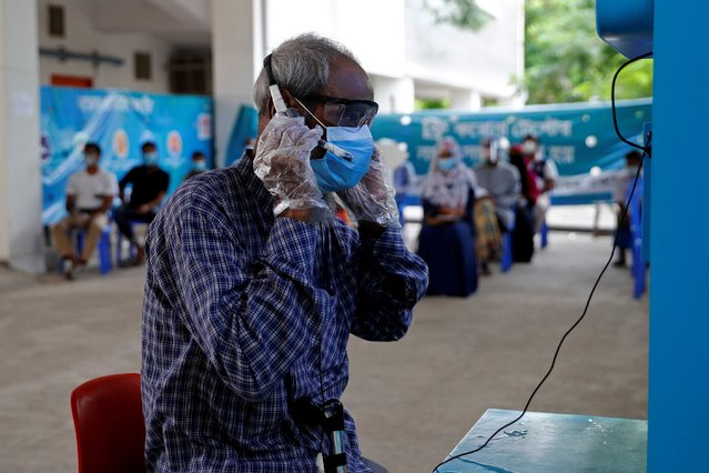 A man wearing a protective mask consults a doctor over video call as he comes for a coronavirus test in the Mugda Medical College and Hospital as the coronavirus disease (COVID-19) outbreak continues in Dhaka, Bangladesh, July 2, 2020. (Photo by Mohammad Ponir Hossain/Reuters)
