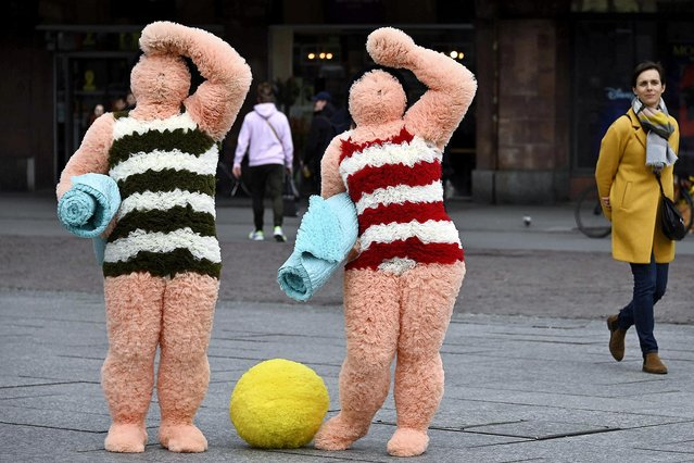 """French artists Coco Petitpierre and Yvan Cledat, equipped with a beach ball and towels, perform a show entitled """"Les baigneurs"""" in Strasbourg, eastern France, on March 11, 2020, as part of the """"Giboulees"""" festival. (Photo by Frederick Florin/AFP Photo)"""