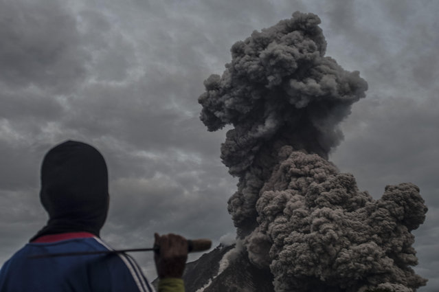 A resident watches the volcanic ash spew into the air as Sinabung volcano erupts in North Sumatra province, Indonesia on September 29, 2015. Residents on Indonesia's Sumatra Island are on alert again after volcano Mt Sinabung erupted in spectacular fashion, sending ash high into the sky. (Photo by Sutanta Aditya/NurPhoto via ZUMA Press)