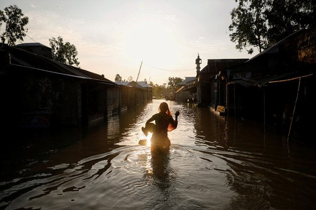 A woman is silhouetted when she walks on a flooded road in Jamalpur, Bangladesh, July 18, 2020. (Photo by Mohammad Ponir Hossain/Reuters)