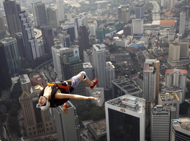 France's base jumper Florian Pays gestures while leaping from Malaysia's landmark KL Tower, the 421-meter (1,389-foot) broadcasting tower in downtown Kuala Lumpur, Malaysia, September 29, 2012. (Photo by Vincent Thian/AP Photo)