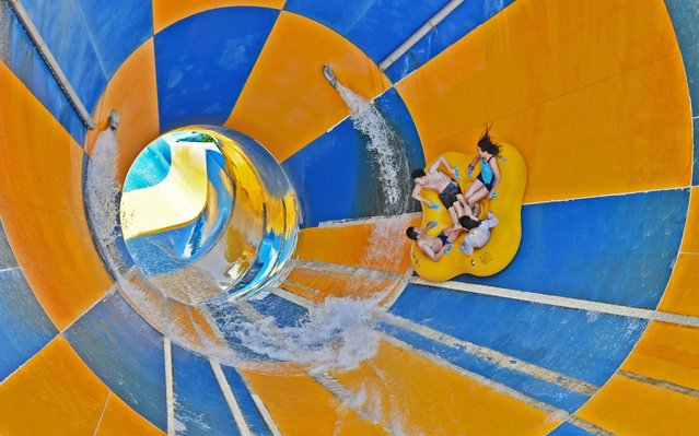 Tourists play at a water slide of 37 Degree Dream Sea Park on July 25, 2020 in Yantai, Shandong Province of China. (Photo by Sun Wentan/VCG via Getty Images)