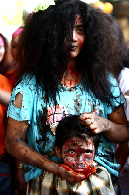 A woman holds a boy posing as a decapitated head during a Zombie Zumba Party in Mandaluyong City, the Philippines, October 26, 2014. (Photo by Rouelle Umali/Xinhua)