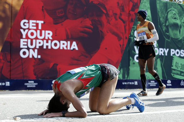 Yuki Kawauchi of Japan drops to his knees after finishing. At right is fourth place finisher Meb Keflezighi of the U.S. (Photo by Mike Segar/Reuters)