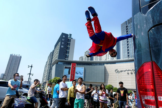 A performer is seen floating in mid-air as he holds onto a moving bus during the International Magic Festival in Luoyang, Henan province, China September 11, 2016. (Photo by Reuters/China Daily)