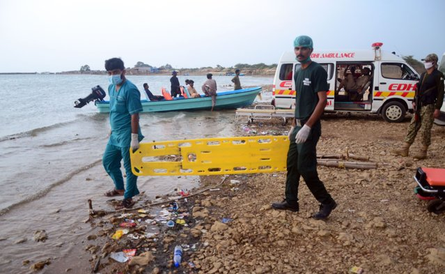 Pakistani paramedics standing on the bank of lake with a stretcher as a boat capsized Pakistan in Thatta district of southern Sindh province, Pakistan, August 17, 2020. At least 10 people died after their boat capsized in a lake in southern Pakistan on Monday, officials said. The boat carrying 13 picnickers turned over in Keenjhar Lake, Thatta district of Sindh province. (Photo by Shakeel Ahmed/Anadolu Agency via Getty Images)