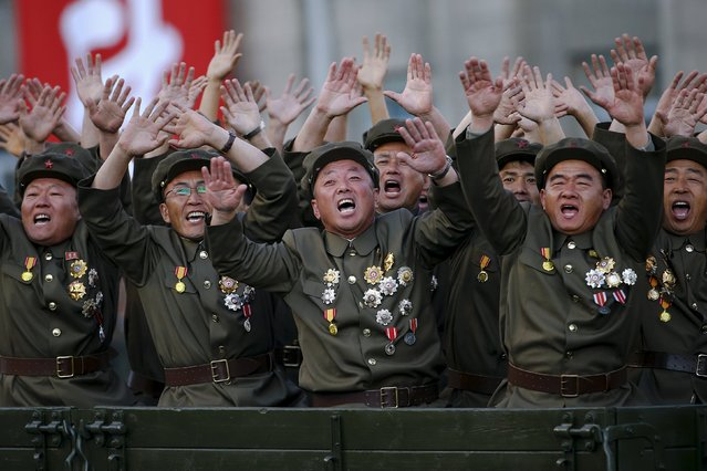 Veteran soldiers react as their truck drives past a stand with North Korean leader Kim Jong Un during the parade celebrating the 70th anniversary of the founding of the ruling Workers' Party of Korea, in Pyongyang October 10, 2015. (Photo by Damir Sagolj/Reuters)