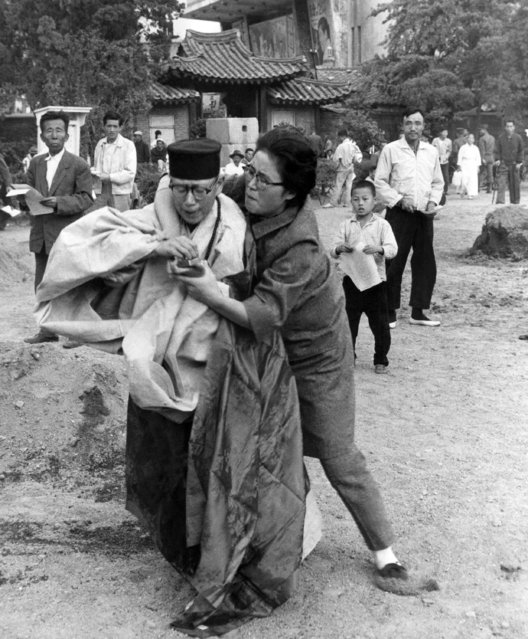 A woman prevents the fiery suicide of a Buddhist nun as she grabs matches from the nun in Seoul, South Korea, October 14, 1963. The nun had drenched herself with gasoline and was preparing to ignite herself when the woman stopped her in Pagoda Park. The suicide was to be a protest against the South Korean government's alleged discrimination against married Buddhist. (Photo by AP Photo)