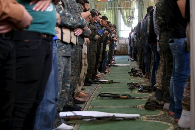 Men pray near their weapons inside a mosque in Salah al-Din neighbourhood in central Aleppo, Syria October 16, 2015. (Photo by Hosam Katan/Reuters)