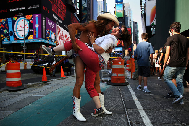 """Robert Burck, a street performer known as """"The Naked Cowboy"""" dips a woman as he poses for a photo in Times Square in New York, U.S., August 4, 2016. (Photo by Carlo Allegri/Reuters)"""