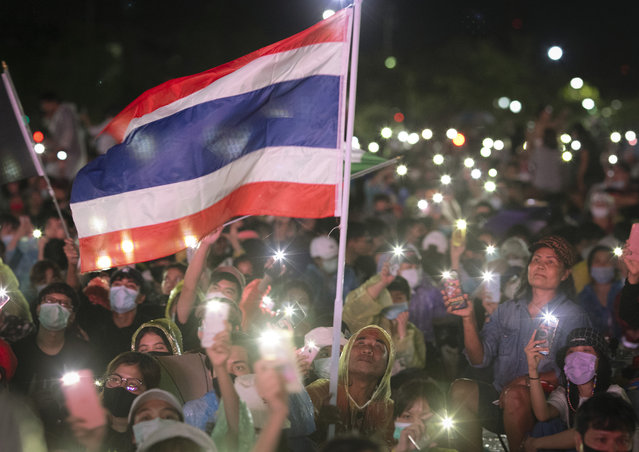 Pro-democracy protesters wave a flag and hold up lights during a protest at Sanam Luang in Bangkok, Thailand, Saturday, September 19, 2020. Thousands of demonstrators turned out Saturday for a rally to support the student-led protest movement's demands for new elections and reform of the monarchy. (Photo by Wason Wanichakorn/AP Photo)