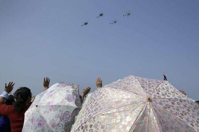 North Korean women carrying parasols wave as Hughes MD-500 helicopters fly past during an aerial display on Saturday, September 24, 2016, in Wonsan, North Korea. (Photo by Wong Maye-E/AP Photo)