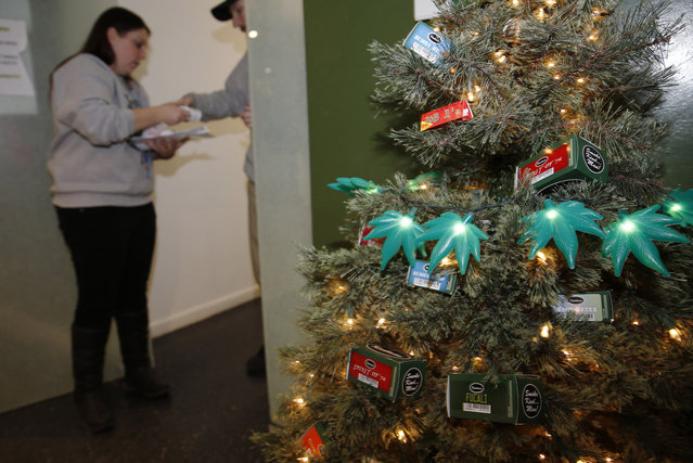 In this photograph taken on Thursday, November 20, 2014, a Christmas tree decorated with lighted marijuana leaves sits in the foreground as bud tenders Maggie Slattery, back left, and John Satterfield check over customer's order in a recreational marijuana shop in northwest Denver. (Photo by David Zalubowski/AP Photo)
