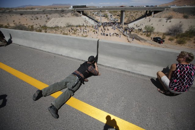 Eric Parker from central Idaho aims his weapon from a bridge as protesters gather by the Bureau of Land Management's (BLM) base camp, where cattle that were seized from rancher Cliven Bundy are being held, near Bunkerville, Nevada in this April 12, 2014 file photo. We were on a bridge in southern Nevada in the midst of a tense standoff between the BLM and a group of angry ranchers, militia members and gun-rights activists. (Photo and caption by Jim Urquhart/Reuters)